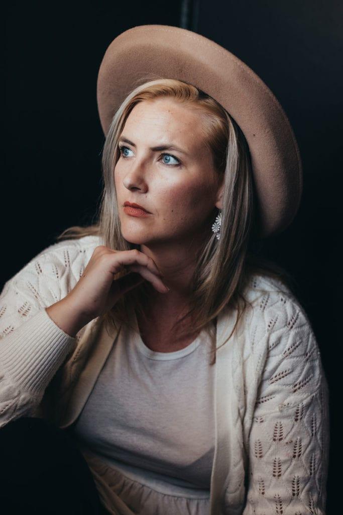 Molly Pasquariello, Senior Photographer, headshot wearing wide brim hat