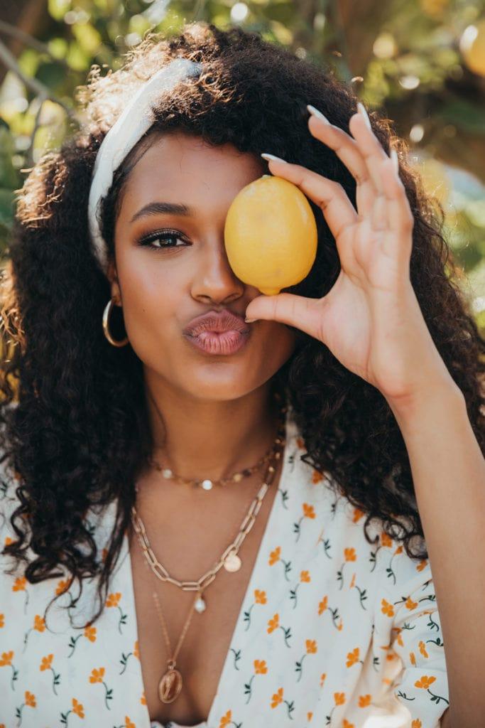 San Diego Senior Photographer, girl holding up lemon in front of her eye